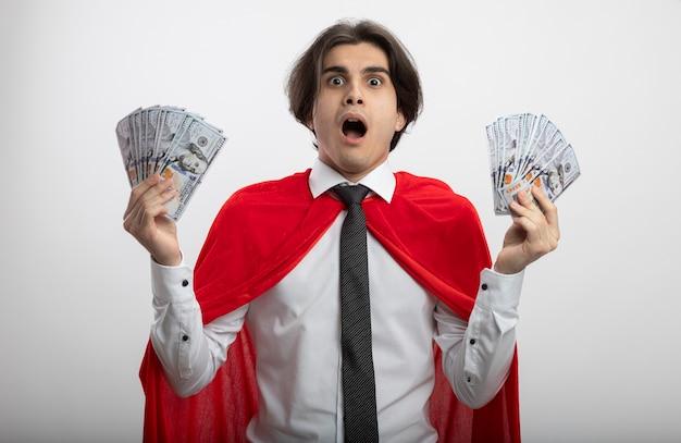 白い背景で隔離のお金を保持しているネクタイを身に着けているカメラを見て怖い若いスーパーヒーローの男
