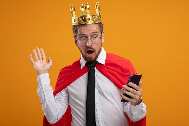넥타이와 왕관을 착용하고 오렌지 배경에 고립 된 측면에서 손으로 전화 및 포인트를보고 안경을 쓰고 무서워 젊은 슈퍼 히어로 남자