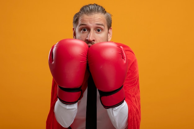 Scared young superhero guy wearing tie and boxing gloves covered face with gloves isolated on orange background