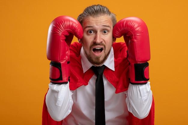 Spaventato il giovane supereroe ragazzo indossa cravatta e guantoni da boxe mettendo le mani sulla testa isolata su sfondo arancione