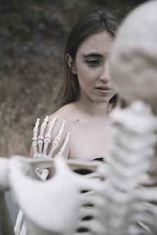 Испуганная молодая женщина за скелетом