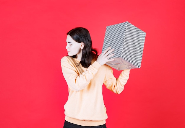Scared young woman holding birthday gift box