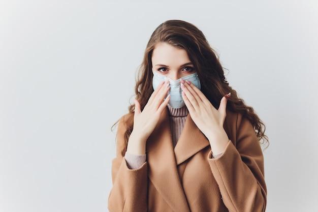 灰色の壁の上に立っている医療マスクで怖がっている若い女性。