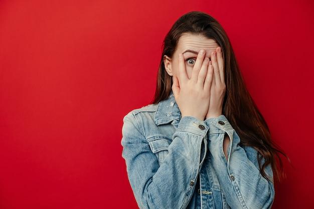 Испуганная молодая женщина, изолированная на красном фоне студии, смотрит сквозь пальцы, испуганно чувствует испуг, смотрит широко раскрытыми глазами, носит джинсовую куртку, прячет лицо от кого-то, копирует пространство в сторону