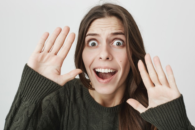 Scared young woman raising hands in surrender, scream ambushed