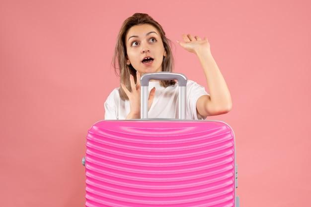 大きなスーツケースの後ろに立っている怖い若い女性