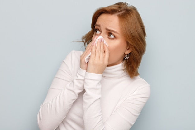 Scared young woman in white turtleneck with napkin blowing nose, looking to the source of allergy.