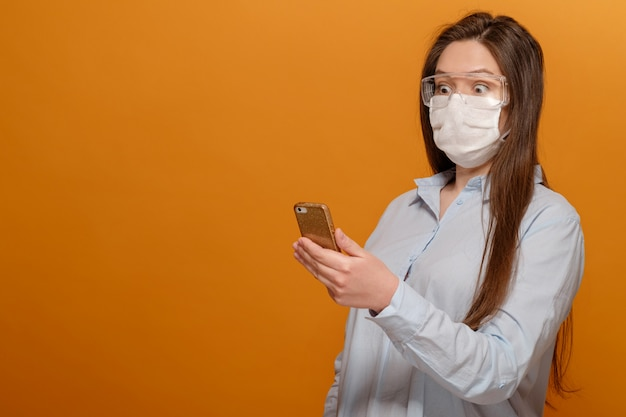 Scared young woman with medical mask on her face looks at phone