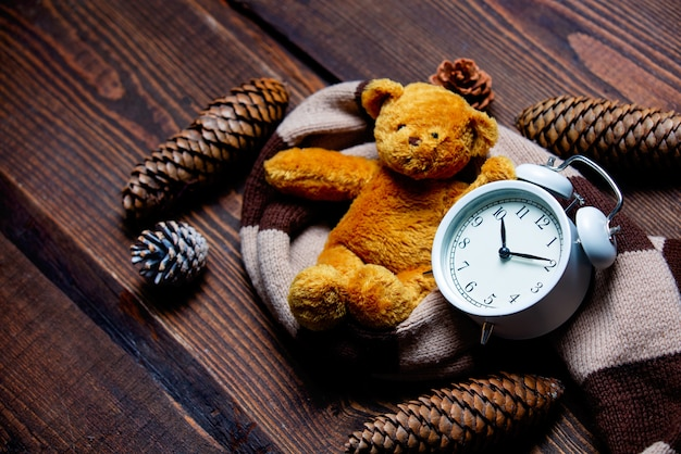 Scarf and alarm clock with teddy bear on wooden table