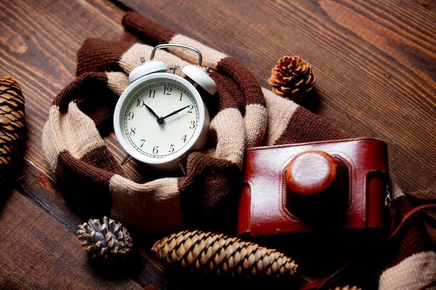Шарф и будильник с шишками и камерой на деревянном столе