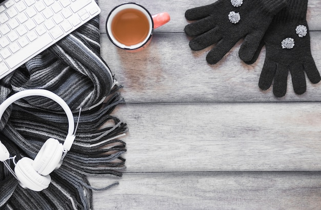 Scarf and gloves near tea and devices