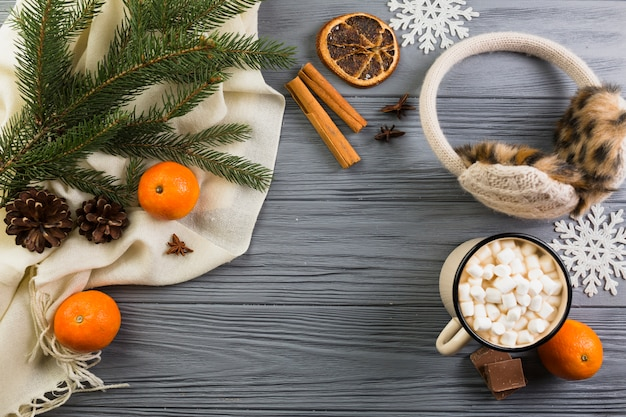 Scarf near cup with marshmallows, earmuffs and fir branch