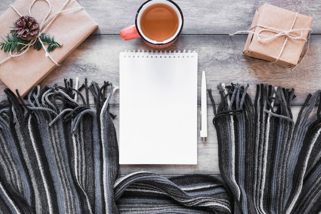 Scarf and notebook near tea and presents