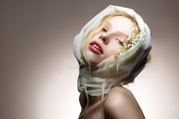 頭にスカーフ。頭に白い絹のスカーフと髪に花でポーズをとる若い青い目のモデル