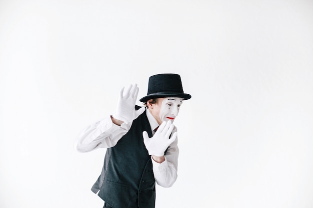 Scarred mime holds his hands up trying to hide from something