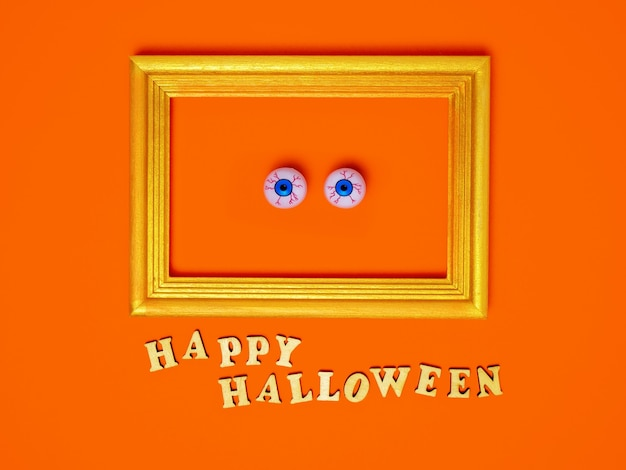 オレンジ色の背景のコピースペースにフレーム幸せなハロウィーンの碑文の怖くて面白い目