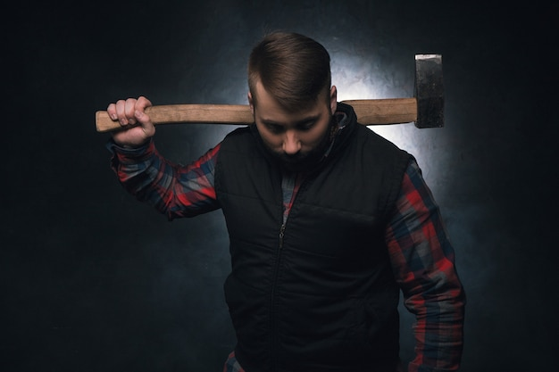 Scary axeman. angry maniac with axe. dangerous rural man on black background closeup, aggressive look, threat concept