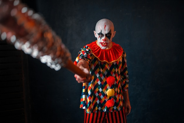 Scary bloody clown reaches out baseball bat. man with makeup in halloween costume, crazy killer