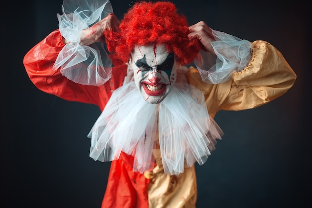 Scary bloody clown tears his hair