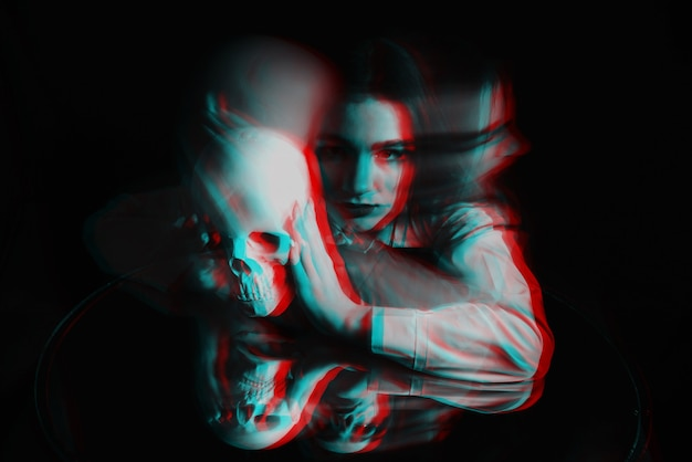 Scary blurry portrait of a female witch with a skull in her hands on a black background. black and white with 3d glitch virtual reality effect