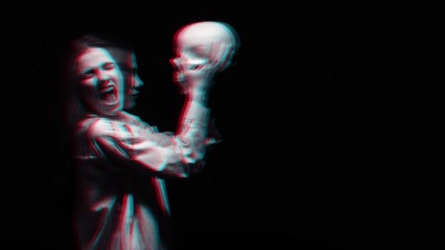 Страшно размытый портрет женщины-ведьмы с черепом в руках на черном фоне. черно-белый с эффектом виртуальной реальности 3d глюк