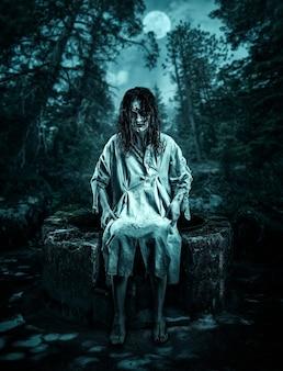 夜の森の井戸に座っている怖い死体。ハロウィーン。