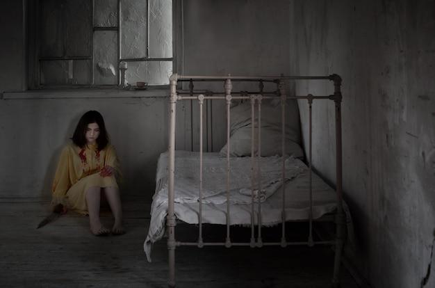 Страшно сумасшедшая девушка, покрытая кровью с ножом в запертой комнате ночью