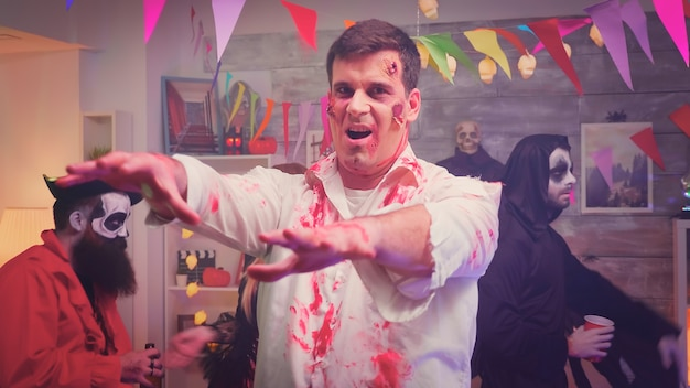Scary and dangerous zombie at halloween party having fun and dancing next to his disguised friends