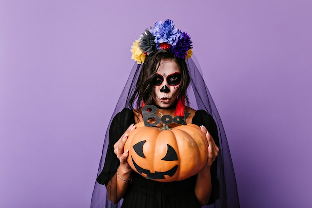 Spaventosa sposa morta tenendo la zucca. donna europea in velo nero in posa sulla parete viola in halloween.
