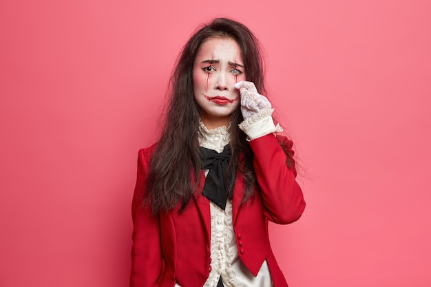 Scary dejected brunette woman with halloween makeup wipes tears has gloomy expression bloody face art wears red jacket and lace gloves white lense on eye poses indoor against rosy wall