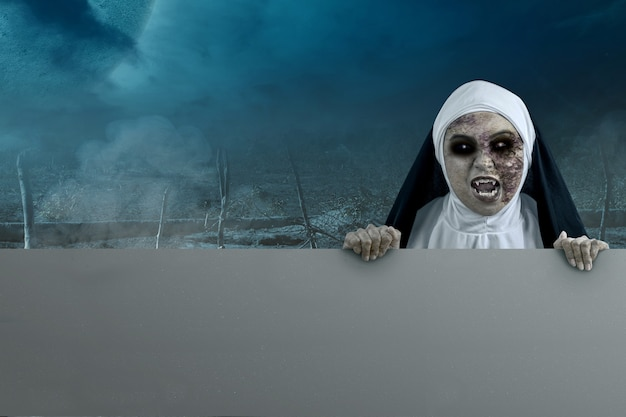 Scary devil nun holding an empty board with night scene background. empty board for copy space