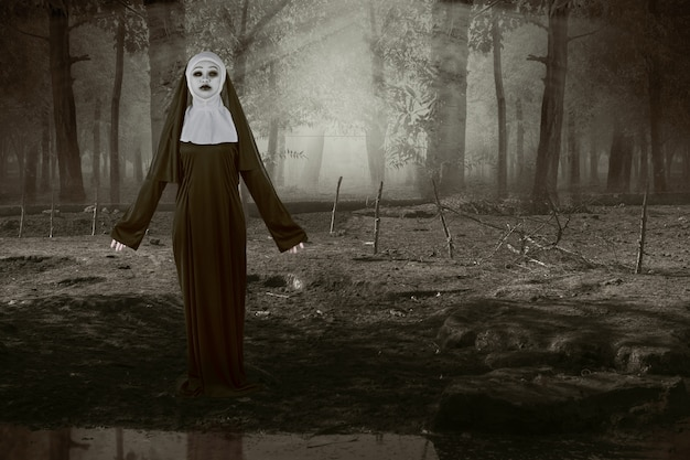 Scary devil nun standing on the haunted forest