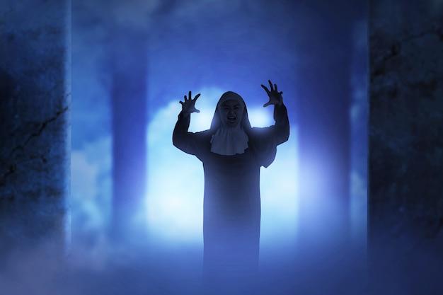 廃墟のビルに立っている怖い悪魔の尼僧。ハロウィーンのコンセプト