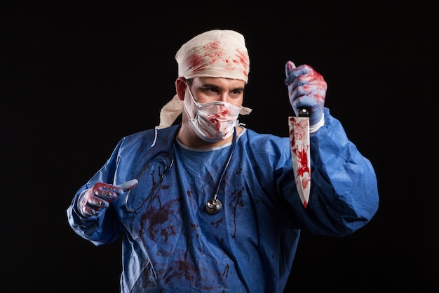 Scary doctor with evil face looking at his knife in studio. man dressed up like a killer doctor for halloween.