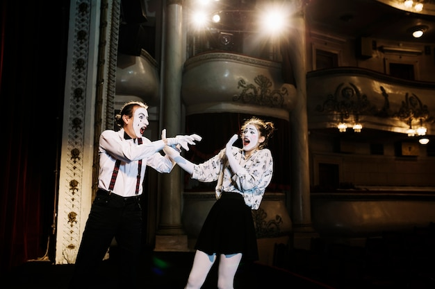 Scary female mime trying to defend from male mime in the auditorium