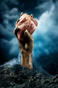 Mano di zombie femmina spaventosa che tiene un cuore
