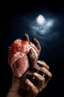 心を持って怖い女性ゾンビの手