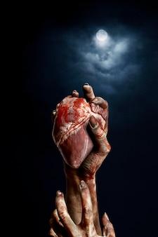 Mani spaventose di zombie femminili che tengono un cuore