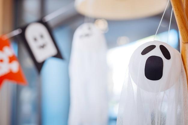 怖い幽霊。思い出に残る面白い子供たちのパーティーのハロウィーンの装飾として使用される怖い白い幽霊のクローズアップ