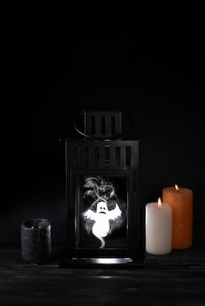 Scary ghost in an old lantern, restless spirit and candles on a black background, halloween concept.