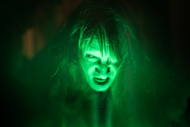 Scary ghost woman screaming through dirty glass on dark background