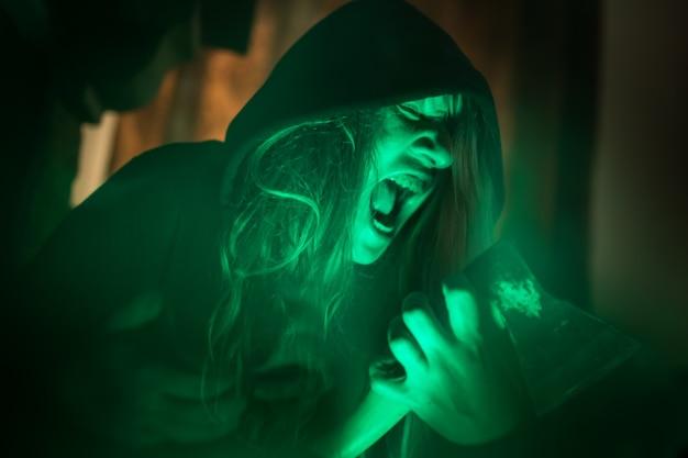 Страшная женщина-призрак кричит через грязное стекло на темном фоне
