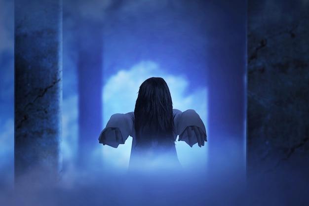 廃墟のビルに立っている怖い幽霊女。ハロウィーンのコンセプト