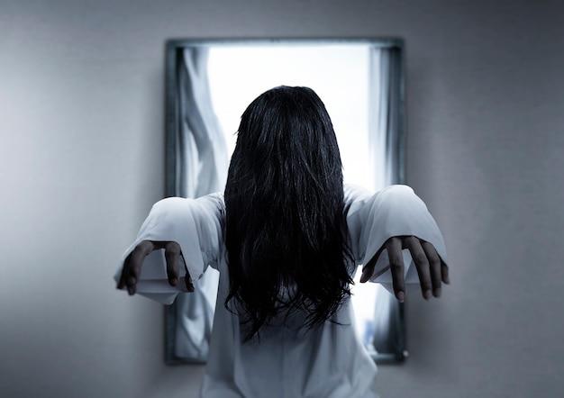 버려진 된 집에 서있는 무서운 유령 여자. 할로윈 개념