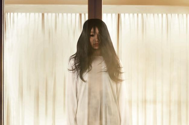 버려진 된 집 할로윈 개념에 서있는 무서운 유령 여자