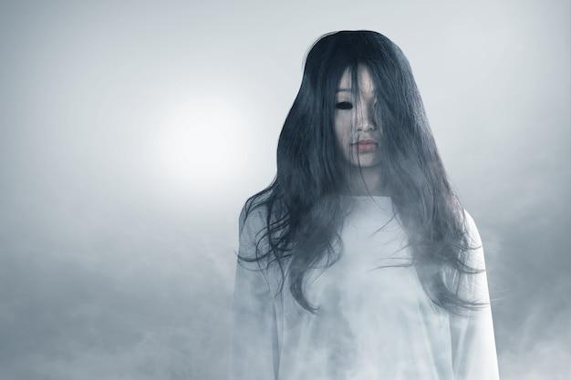 안개 할로윈 개념에 서있는 무서운 유령 여자
