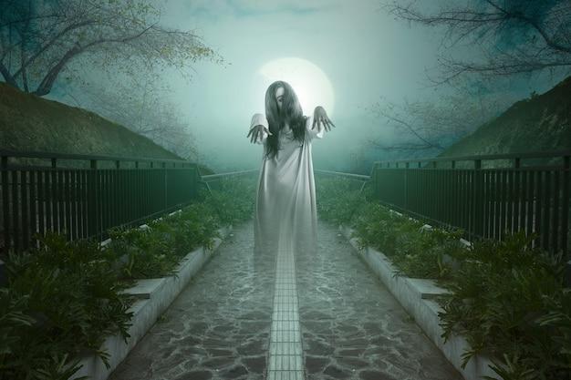 霧と月明かりの背景で小道に立っている怖い幽霊の女性。ハロウィーンのコンセプト