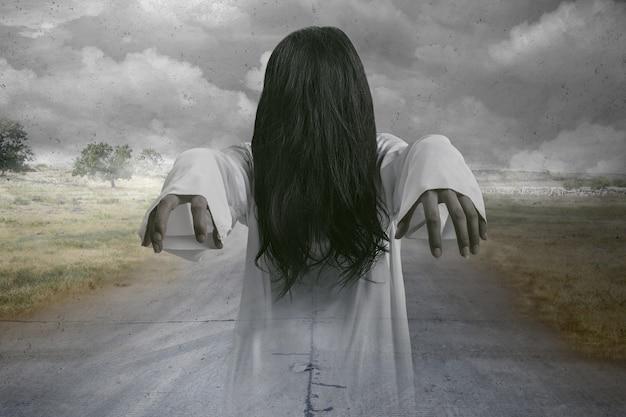 어두운 구름 배경으로 서 있는 무서운 유령 여자. 할로윈 컨셉