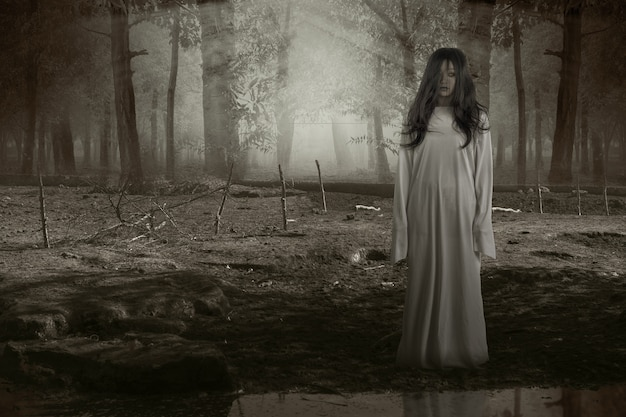 Scary ghost woman standing with haunted forest