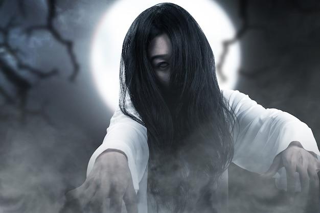 夜のシーンの背景で立っている怖い幽霊の女性。ハロウィーンのコンセプト